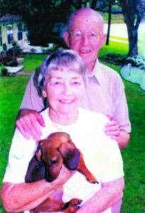 A photo of a senior man standing behind a senior woman, and a senior woman holding a dachshund, posing for a photo