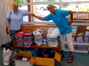 Ann Gillis and Jean Crowley prepare the donations of bookbags, notebooks and school supplies to the local elementary school