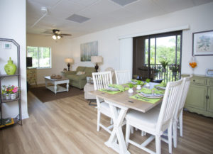 A photo of the dining room, deck, and living room of a spacious senior apartment at the John Knox Village of Central Florida senior living community