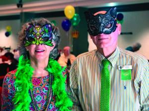 Seniors wearing Mardi Gras masks at a masquerade at the John Knox Village of Central Florida retirement community