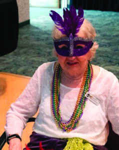 A senior woman with beads and a mask, ready to celebrate Mardi Gras