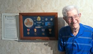 A photo of Jake Beard next to his awards and medals for his military service