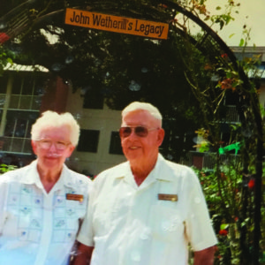 """An old photo of two seniors under a vine arch that reads, """"John Wetherill's Legacy"""""""