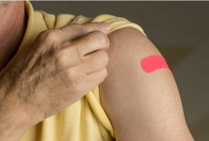 A photo of a senior woman pulling back her short sleeved shirt to reveal her band-aid