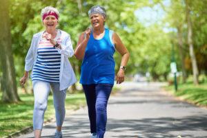 Two senior women go for a walk outside wearing athletic gear