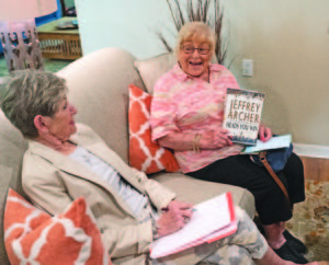 Photos of a senior book club, with a senior woman holding up the book Heads You Win by Jeffrey Archer