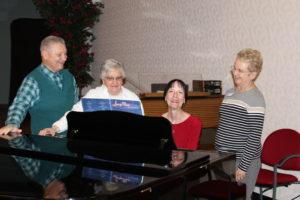 Seniors gathered around a baby grand piano singing holiday songs
