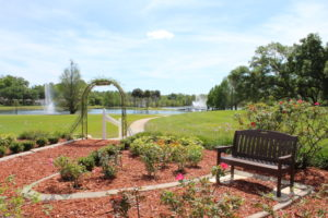 A perfect summer day on the manicured grounds, with seating areas by the rose garden and two fountains in the small lake at the John Knox Village of Central Florida senior living community