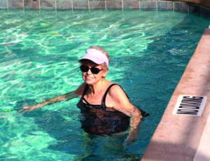 A woman swims in the outdoor pool at the John Knox Village of Central Florida senior living community