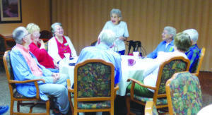Seniors gathering for some conversation and laughter in a dining hall