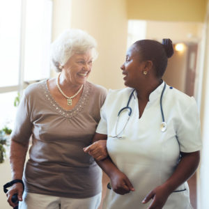 A senior woman is linked arms with a female clinician or physician