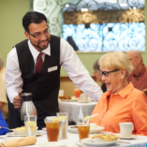 A photo of a server topping off the coffee cups of seniors eating breakfast at the John Knox Village of Central Florida retirement community