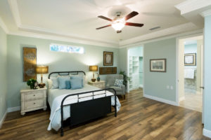 A furnished and spacious bedroom with walk in closed and master bathroom at the John Knox Village of Central Florida