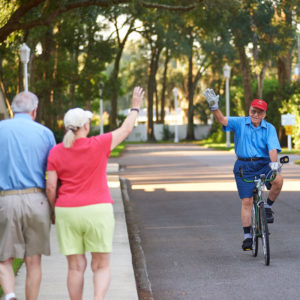 An elderly man biking, raising his hand in greeting to a senior couple on a walk in their senior living neighborhood at the John Knox Village of Central Florida retirement community