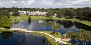 An aerial view of the lake, palm trees, and paved walking path in nature at the John Knox Village of Central Florida