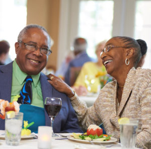 A senior couple laughing and talking while enjoying dinner at the John Knox Village of Central Florida