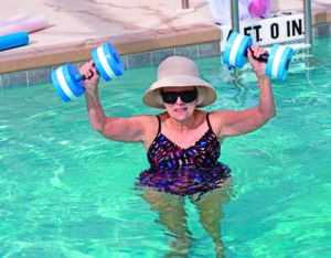 A woman working out in an outdoor swimming pool