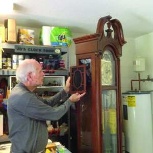 A photo of JD repairing a large grandfather clock