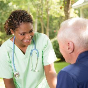 A physician or clinician greeting an elderly man
