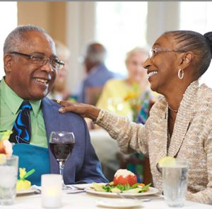 A senior man and senior woman laugh and smile while enjoying dinner