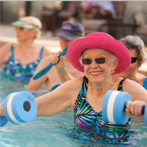 Seniors in an outdoor pool partaking in an water exercise class