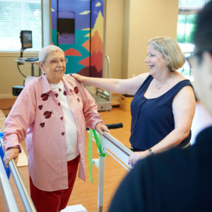 A senior woman is practicing her balancing exercises at a rehabilitation center for seniors