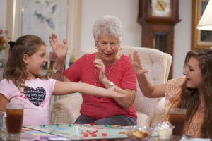 A senior woman and her grandchildren playing a Monopoly