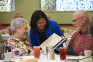 A server helping two seniors make a decision on what they want to order for lunch