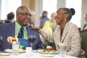 Two seniors smiling and enjoying their dinner