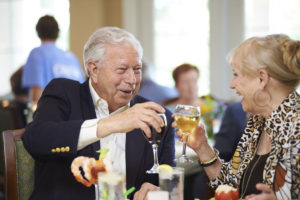A senior man and senior woman toasting with a glass of red and white wine