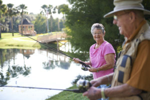 A senior man and a senior woman fishing in the pond at the John Knox Village of Central Florida