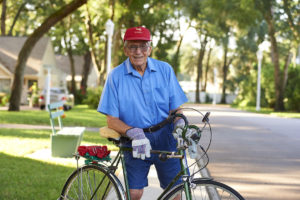 An elderly man riding his bicycle