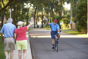 A senior couple walking wave to an elderly man riding his bicycle