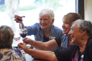 Seniors toasting with red wine