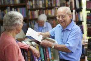 A senior stops to talk to a senior woman about a book in a library or bookstore