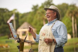 A senior man painting an outdoor scene