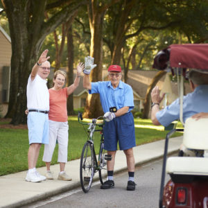 A photo of a senior on a bike and a senior couple waving to their neighbors on a golf cart