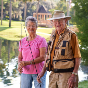 An elderly man and elderly woman are fishing
