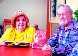 A photo of two seniors in a book club, a senior man holding up a book by Susan Wittig Albert