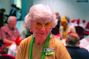 An elderly woman with wine glasses mardi gras mask