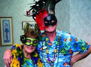 Senior couple celebrating Mardi Gras with masquerade masks and mardi gras beads