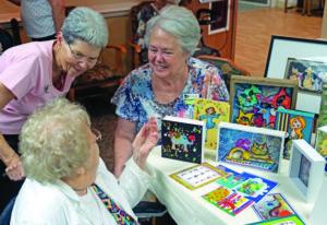 A senior resident showcases her painting skills
