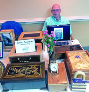 A picture of Glenn Foreman showcasing his intricate woodworking and designs