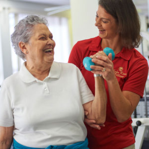 A senior woman is being helped with her physical therapy exercises by female physical therapist