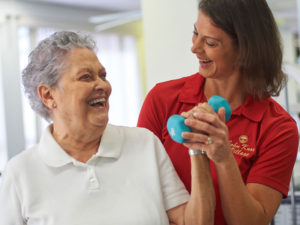 A physical therapist helping a senior woman workout