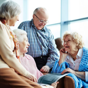 Four seniors, 3 women and one man, looking at a photo book together