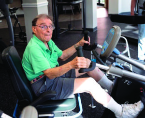A senior man using a biking machine to work out in the fitness room at the John Knox Village of Central Florida retirement community