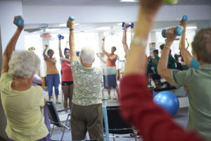 Seniors practicing balance and core strengthening exercises at a fitness class