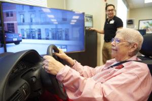 A senior woman playing a car driving simulator
