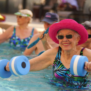 Seniors in an outdoor pool exercising with weights
